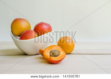 Apricots in white bowl with one apricot cut open.