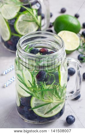 Healthy cold infused water with fresh blueberry lime and rosemary vertical