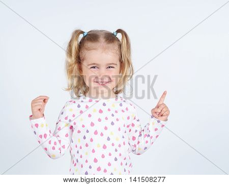 little girl wearing pointing by forefinger to somewhere up isolated
