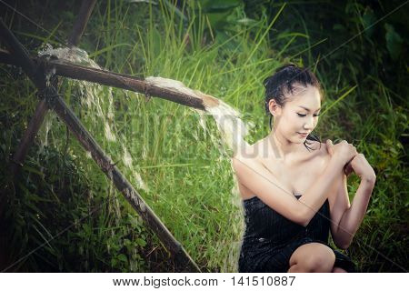 Sexy woman bathing in cascade at in the countryside in asia
