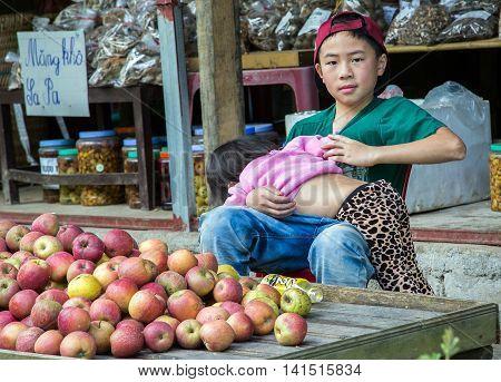 SAPA LAO CAI VIETNAM - NOV 21 2014: Children from Dao minority group wearing traditional headdress near Ban Ho village Sa pa District Lao Cai Vietnam.