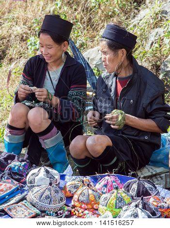 LAO CAI VIETNAM - NOV 21 2014: Woman from Hmong minority group wearing traditional headdress near Sapa Lao Cai Vietnam.