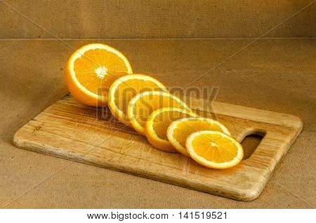 Sliced fresh orange slices on a kitchen light wooden board