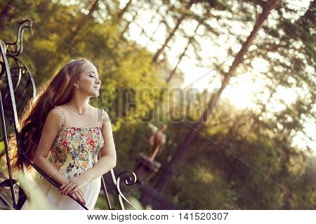 Beautiful European pregnant woman is leaning on the railing and turning the face to the rays of the evening sun. She in floral dress enjoying contact with nature