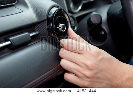 Close-up Of Human Hand Adjusting Air Condition In The Car