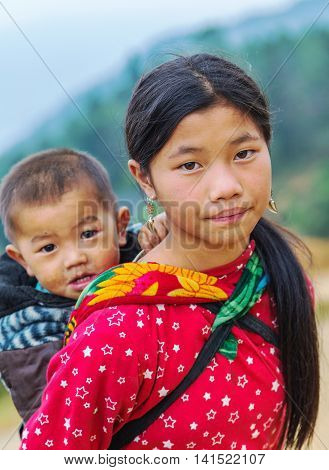 SAPA LAO CAI VIETNAM - NOV 21 2014: Woman from Black Hmong Hill Tribe children girl smile famous tourist destination in Vietnam Sa pa District Lao Cai Vietnam.