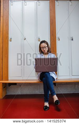 Young woman using laptop in locker room at college