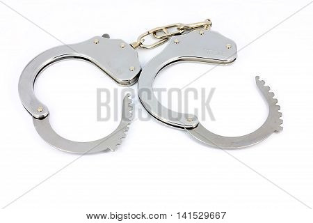 Silver shiny pair of open police handcuffs