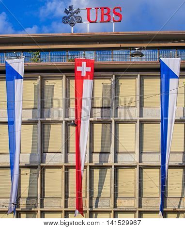 Zurich, Switzerland - 30 July, 2016: facade of the UBS building on Talacker street decorated with flags of Switzerland and Zurich, view from Paradeplatz square. UBS AG is a Swiss global financial services company, incorporated in the Canton of Zurich.