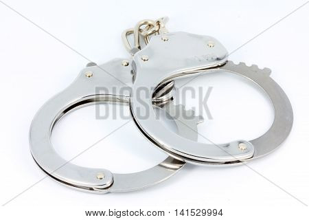 Silver shiny pair of handcuffs isolated on white
