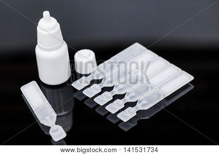 Lubricant eye drops vials and eye drop bottle on black background