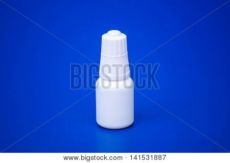 Eye drop bottle isolated on blue background