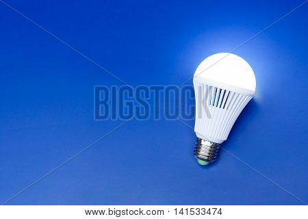 A turned on LED light bulb on blue background / Using economical and environmentally friendly light bulb concept
