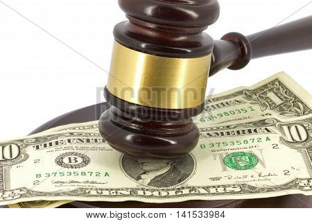 Wooden gavel with sound block and dollars
