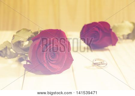 Two red roses and rings on wooden background