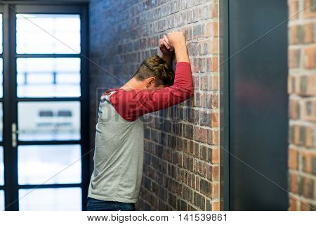 Side view of stressed man leaning on wall in building