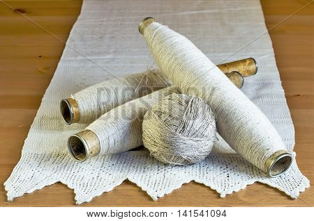 Vintage spools with linen threads and handmade tablecloth with lace on a wooden background.