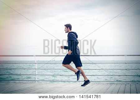 Side view portrait of a sports man running near sea
