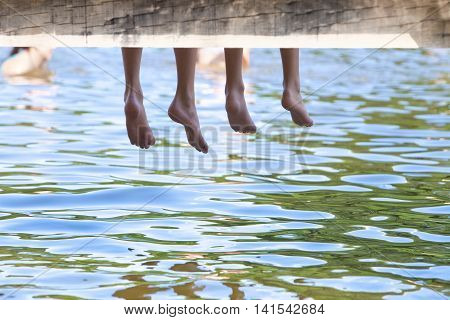 Boys sitting on a pier with legs dangling