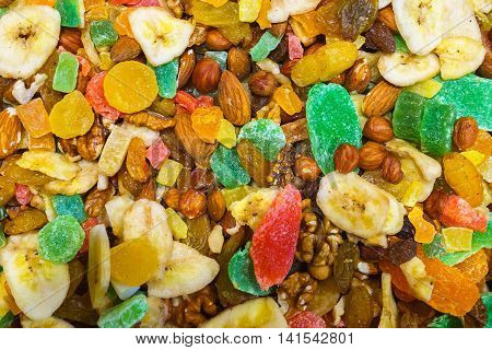A set of dried fruit for the diet. Dried bananas raisins grapes plums dates Mendal hazelnuts walnuts sweet mixture.
