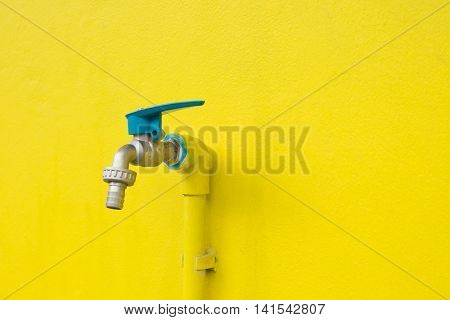 Closeup faucet on concrete Yellow wall background. Tap closeup with dripping water-drop. Water leaking saving concept.