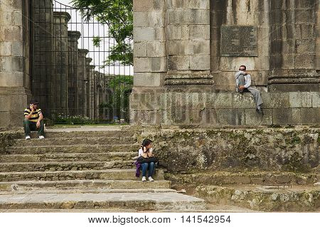 CARTAGO, COSTA RICA - JUNE 17, 2012: Unidentified people sit at the entrance to the ruins of the Santiago Apostol cathedral in Cartago, Costa Rica.