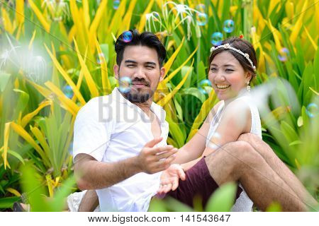 happy asian couple play together with bubble in garden
