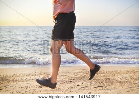 Young man running on the beach at sunset