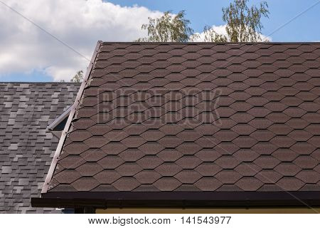 Part of red bitumen tiles roof in sunny day