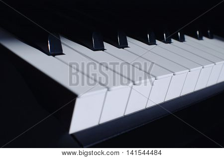 a piano instrument black and white keys with a blue tint