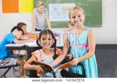 Portrait of school kids holding book in classroom at school