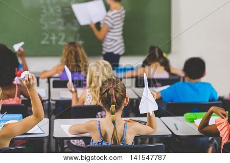 school kids with paper planes while teacher teaching in classroom at school