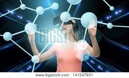 technology, virtual reality, cyberspace and people concept - happy young woman with virtual reality headset or 3d glasses touching projection of molecule over black background and laser light