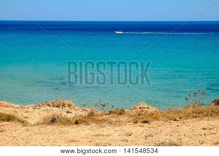 Seascape with blue sea water and a white boat. Location Pinus Village in Sardinia Italy.