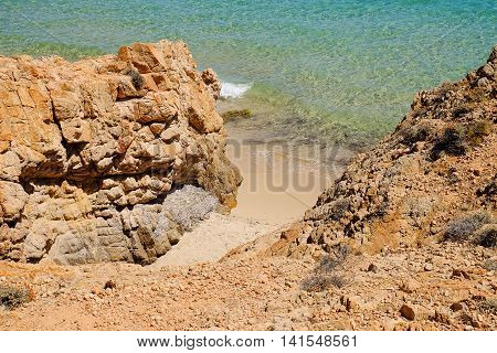 View on a small sand beach between the rocks and a crystal emerald sea water in Pinus Village in Sardinia Italy.