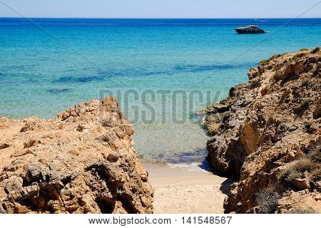 View on a small sand beach between the cliffs and blue sea with a boat in Pinus Villahe in Sardinia Italy.