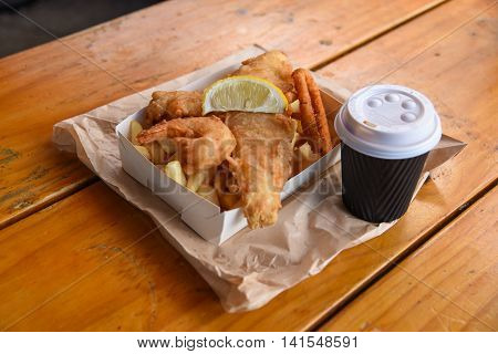 fish and chips meal set with coffee on wooden table