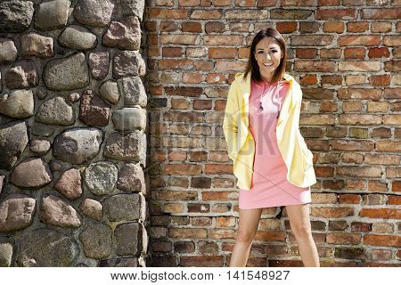 Smiling Woman Against A Brick Wall