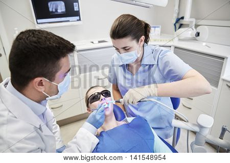 people, medicine, stomatology and health care concept - male dentist and assistant with dental curing light and mirror treating female patient teeth at dental clinic office