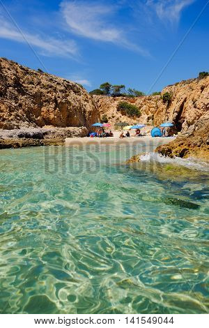 Small beach between the rocks with colorful sun umbrellas and an unknown persons. Pinus Village in Sardinia Italy.02.08.2016.