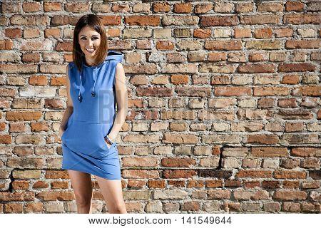 Woman In Blue Dress Against A Brick Wall