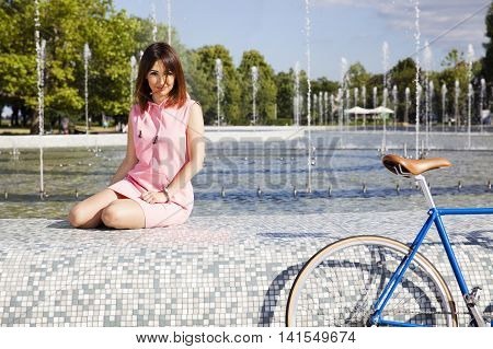 Attractive Girl Sitting On The Fountain
