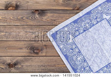 Blue arabic cloth with ornament on a wooden table, top view