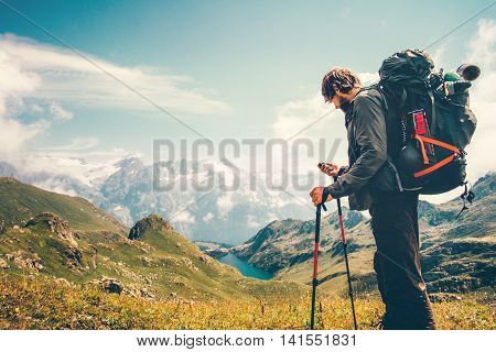 Man Traveler backpacker with gps navigator tracker looking for coordinates Travel Lifestyle concept mountains and lake on background survival adventure vacations outdoor