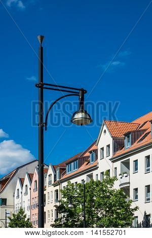 Buildings with lantern in Rostock (Germany) with blue sky.