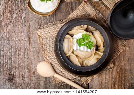 Meat Dumplings - russian pelmeni with sour cream on rustic background, top view