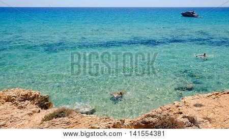 View from above on the rocks and the beach in Pinus Village and swimming unknown persons.
