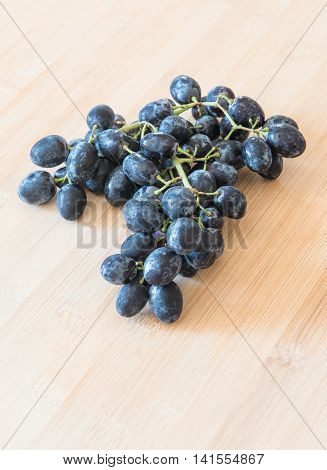 Branch of healthy black fresh grape fruits use to produce wine on a wooden board.