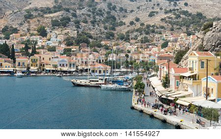 Symi Greece - August 8 2016: Panoramic image of Symi town with colorful houses on the hill in the Greek Island of Symi at the Aegean sea.