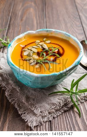 Roasted pumpkin soup with balsamic and pumpkin seeds on wooden background, close up